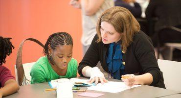 معلم در حال آموزش به دانش آموز دختر