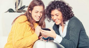 دو دختر در حال نگاه کردن به تبلت